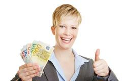 La mujer con la tenencia de dinero euro manosea con los dedos para arriba Fotos de archivo libres de regalías