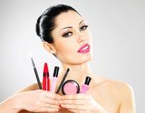 La mujer con las herramientas cosméticas del maquillaje acerca a su cara. Imagen de archivo