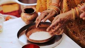La mujer con las manos en mehendi pone el arroz en la placa de bronce almacen de metraje de vídeo