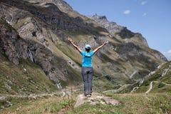 La mujer con las partes posteriores abre los brazos en un paisaje montañoso imagen de archivo libre de regalías