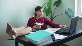 La mujer con las piernas en el escritorio almuerza mientras que trabaja metrajes