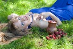 La mujer con leche y una fresa Fotos de archivo libres de regalías