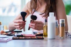 La mujer con los accesorios del maquillaje en concepto de la belleza Imágenes de archivo libres de regalías
