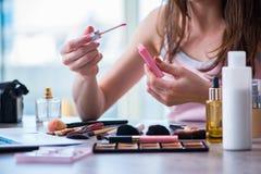 La mujer con los accesorios del maquillaje en concepto de la belleza Fotos de archivo libres de regalías