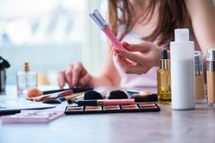 La mujer con los accesorios del maquillaje en concepto de la belleza Fotografía de archivo libre de regalías