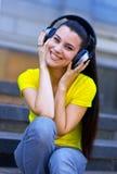 La mujer con los auriculares escucha música Imagenes de archivo