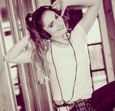 La mujer con los auriculares escucha música y baila Fotografía de archivo libre de regalías