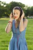 La mujer con los auriculares que escucha la música cerrada observa sobre árbol Imagen de archivo