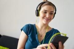 La mujer con los auriculares verdes escucha música del podcast en el teléfono fotos de archivo