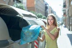 La mujer con los bolsos de basura acerca al compartimiento de basura Imagenes de archivo