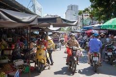 La mujer con los bolsos de compras está montando la moto en el mercado mojado Imágenes de archivo libres de regalías