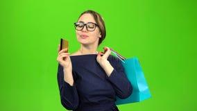 La mujer con los bolsos del papel va a hacer compras con una tarjeta en sus manos Pantalla verde metrajes