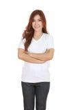 La mujer con los brazos cruzó, llevando la camiseta blanca Imagenes de archivo