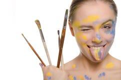 La mujer con los cepillos y la pintura en cara muestra la lengüeta fotografía de archivo