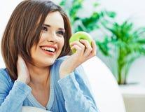 La mujer con los dientes sanos blancos que sonríe, sostiene la manzana verde Fotografía de archivo