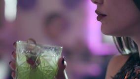 La mujer con los labios atractivos bebe el cóctel verde con un vidrio transparente en el primer de la noche almacen de video