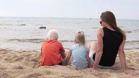 La mujer con los niños se sienta en la playa y las miradas en el mar almacen de metraje de vídeo