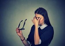 La mujer con los vidrios que la frotan los ojos siente cansada Imagen de archivo libre de regalías