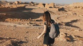 La mujer con la mochila explora ruinas antiguas del desierto El turista europeo hermoso camina en rocas y la arena Masada Israel  metrajes