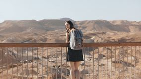 La mujer con la mochila mira Mountain View masivo La muchacha bastante caucásica disfruta de panorama increíble del desierto Isra metrajes