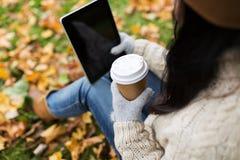 La mujer con PC de la tableta y el café en otoño parquean Foto de archivo libre de regalías