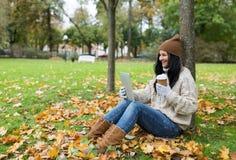La mujer con PC de la tableta y el café en otoño parquean Fotografía de archivo