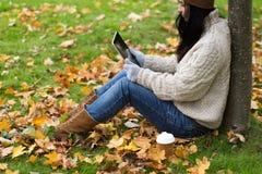 La mujer con PC de la tableta y el café en otoño parquean Imágenes de archivo libres de regalías