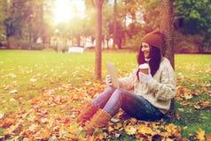 La mujer con PC de la tableta y el café en otoño parquean Imagenes de archivo