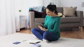 La mujer con PC de la tableta y el viaje empaquetan en casa almacen de metraje de vídeo