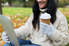 La mujer con PC de la tableta y la taza de café en otoño parquean Imagen de archivo libre de regalías