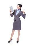 La mujer con PC de la tablilla y la demostración manosean con los dedos para arriba Foto de archivo libre de regalías