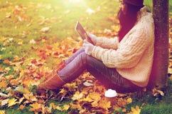 La mujer con PC de la tableta y el café en otoño parquean Fotos de archivo
