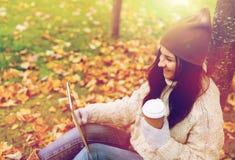 La mujer con PC de la tableta y el café en otoño parquean Imagen de archivo