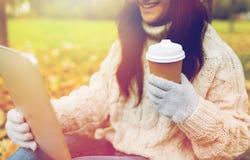 La mujer con PC de la tableta y la taza de café en otoño parquean Imágenes de archivo libres de regalías