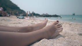 La mujer con pedicura exacta relaja la mentira en la arena caliente almacen de video
