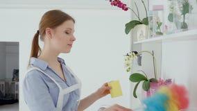 La mujer con polvo de la limpieza del plumero del estante en el hotel se reduce más almacen de video