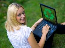 La mujer con recicla insignia en la computadora portátil Imagen de archivo libre de regalías