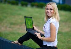 La mujer con recicla insignia en la computadora portátil Fotografía de archivo