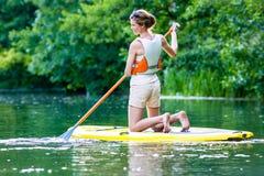La mujer con se levanta sorbo del tablero de paleta en el río Imagen de archivo libre de regalías