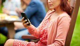 La mujer con smartphone y los amigos en el verano van de fiesta Foto de archivo libre de regalías