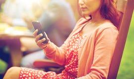 La mujer con smartphone y los amigos en el verano van de fiesta Imagen de archivo