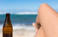 La mujer con sus piernas cruzó, relajándose en una playa arenosa hermosa Fotografía de archivo