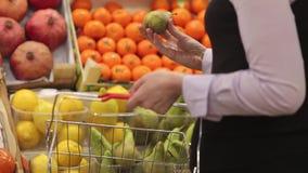 La mujer con un carro de la compra hace compras en la fruta metrajes