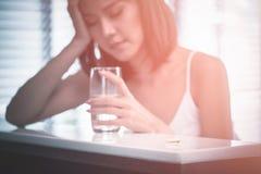 La mujer con un dolor de cabeza sostiene el vidrio de agua, de profundidad y de bajo, foco en píldora Foto de archivo