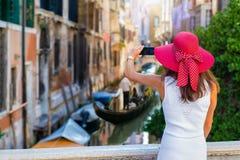 La mujer con un sunhat rojo toma las imágenes de los pequeños canales de Venecia fotografía de archivo