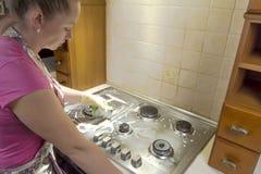 La mujer con un trapo limpia una estufa de gas Imagen de archivo