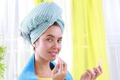 La mujer con un turbante azul aplica el lápiz labial Fotografía de archivo