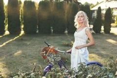 La mujer con una bicicleta camina a través del parque fotos de archivo