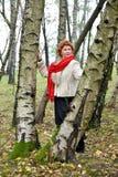 La mujer con una bufanda del rojo cuesta entre abedules en la madera Foto de archivo