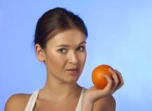 La mujer con una fruta anaranjada Fotografía de archivo libre de regalías